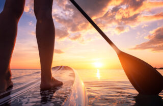 Stand up paddle boarding or standup paddleboarding on quiet sea at sunset with beautiful colors during warm summer beach vacation holiday, active woman, close-up of water surface, legs and board